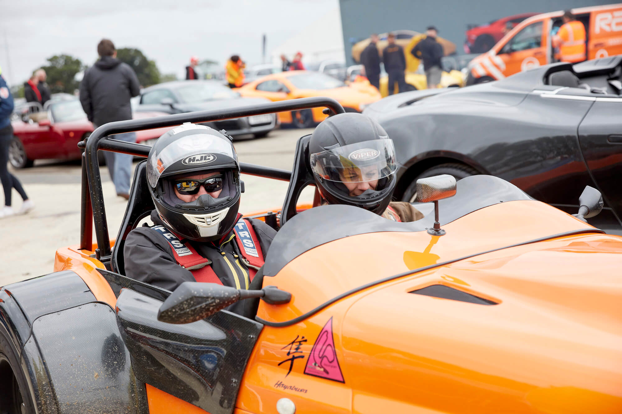 Two people with helments on driving off in an open-topped two-seater orange car as part of the Dream Rides activity at The Classic at Silverstone