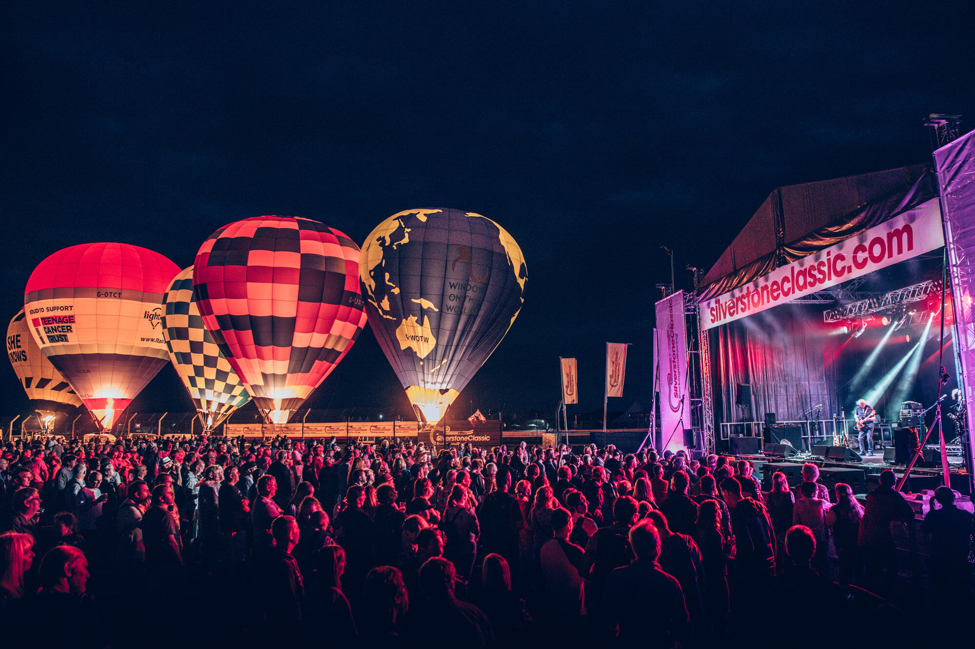 A large crowd gathered in the evening in front of the concert stage at The Classic at Silverstone with hot air balloons lit up in the background