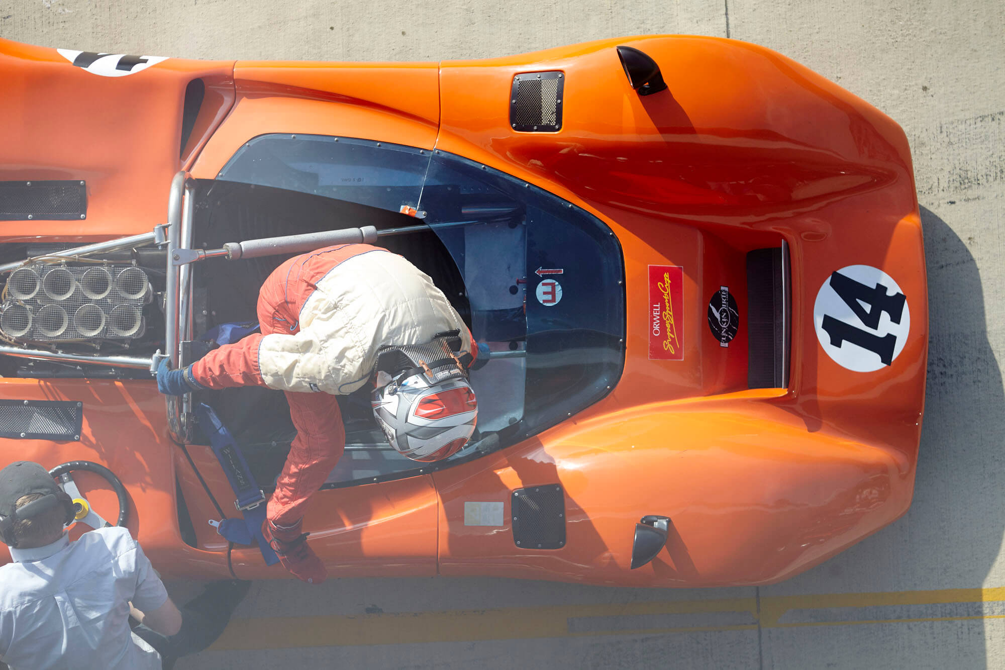 Aerial image of a race competitor climbing out of a classic orange race car at The Classic at Silverstone