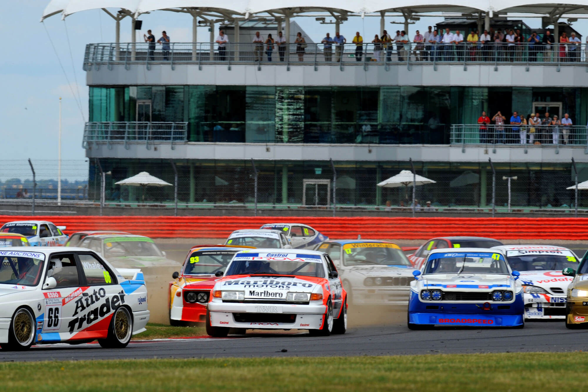 Classic cars racing in the Historic Touring Car Challenge in front of the BRDC building at The Classic at Silverstone