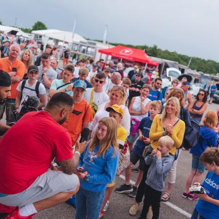A crowd of people watching Yianni on stage at The Classic Silverstone