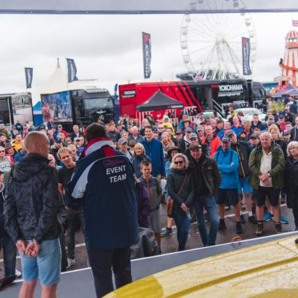 A crowd of people watching a Mike Brewer on stage at The Classic Silverstone