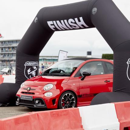 A red Abath driving through the start line of the Abarth Driving Experience at The Classic Silverstone