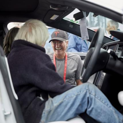 A smiling man taking to some passengers in a Tesla on a Drive Live experience at The Classic Silverstone