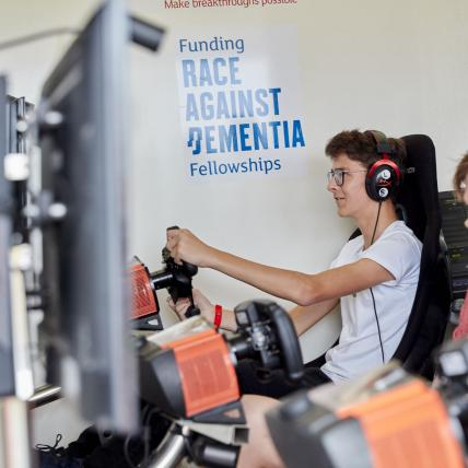 Two teenage boys driving race simulators at The Classic Silverstone