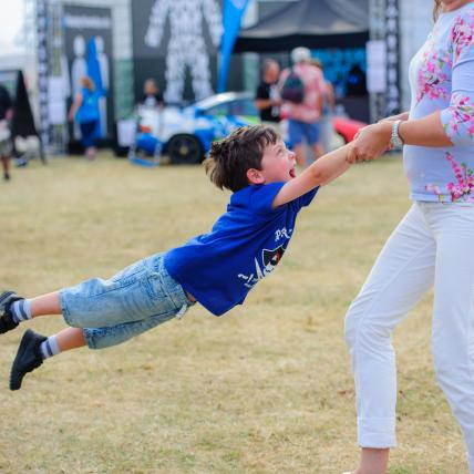 A young boy being spun around playfully in the air by his mother on the Village Green at The Classic Silverstone