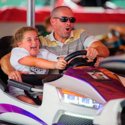 A father and daughter looking excited driving the dodgems at The Classic at Silverstone
