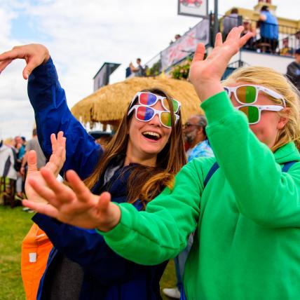 Two girls looking happy and dancing to music at The Classic at Silverstone