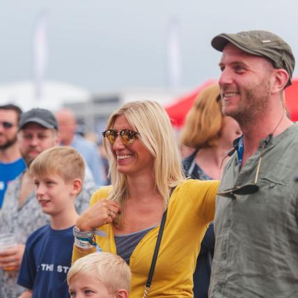 A family smiling whilst watching a demonstration at The Classic at Silverstone