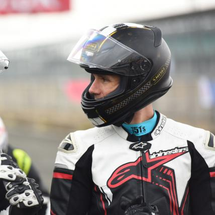 Riders discussing track day in leathers and helmets