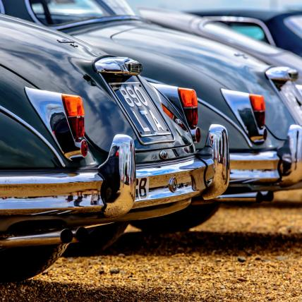 A line-up of brightly coloured classic morgans displayed as part of a Car Club at The Classic at Silverstone