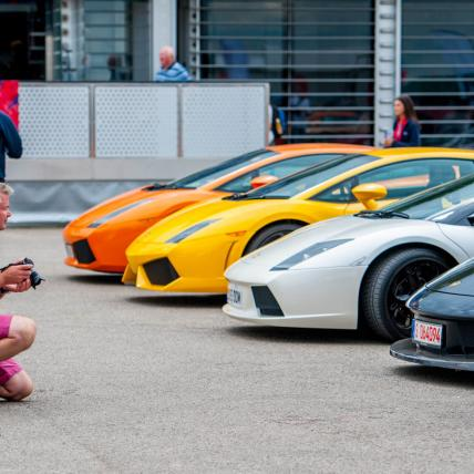A line-up of brightly coloured classic cars displayed as part of a Car Club at The Classic at Silverstone and a man photographing the cars