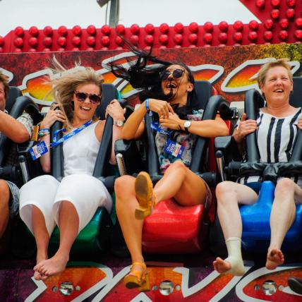 Five adults looking happy on a funfair ride at The Classic Silverstone
