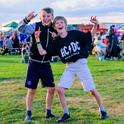 Two young boys looking happy and posing infront of a camera on the Village Green at The Classic