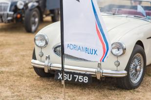 An Adrian Flux flag in front of a cream classic car on display at The Classic at Silverstone