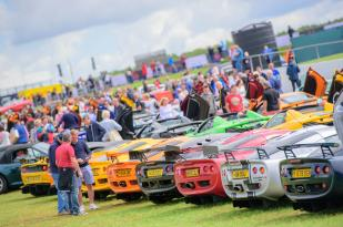 A line-up of brightly coloured classic cars displayed as part of a Car Club at The Classic at Silverstone and a crowd of people looking at the display